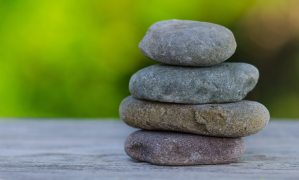 Balancing Stones. Four stones stacked on wooden surface. Blurred green nature background.
