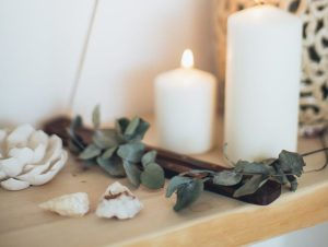 Spa counter with white lit candles, green leaves, sea shells with white background.