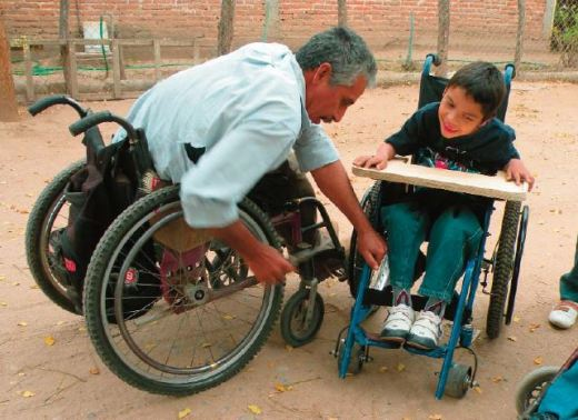 Raymundo, leader of the PROJIMO Duranguito workshop, adjusts a wheelchair that the team made for this boy.