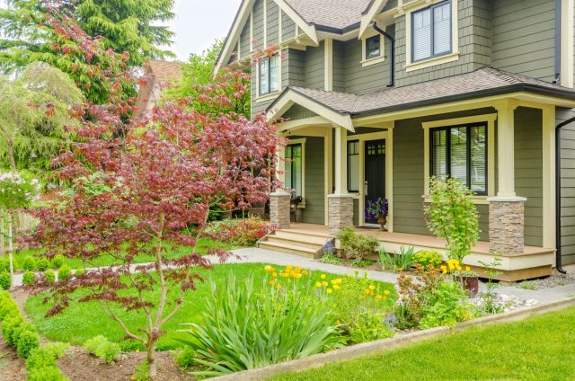 Exterior of a green home with a well maintained front yard.