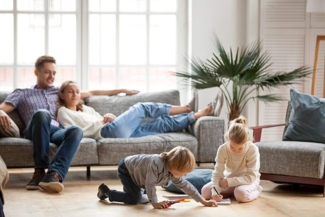 Happy and healthy family sitting and playing in a living room.
