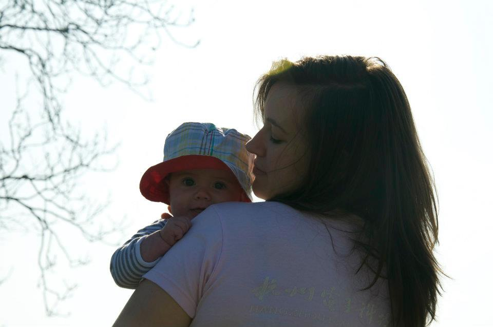 Bible verses about mothers - a mom in profile holding her baby in a floppy hat.