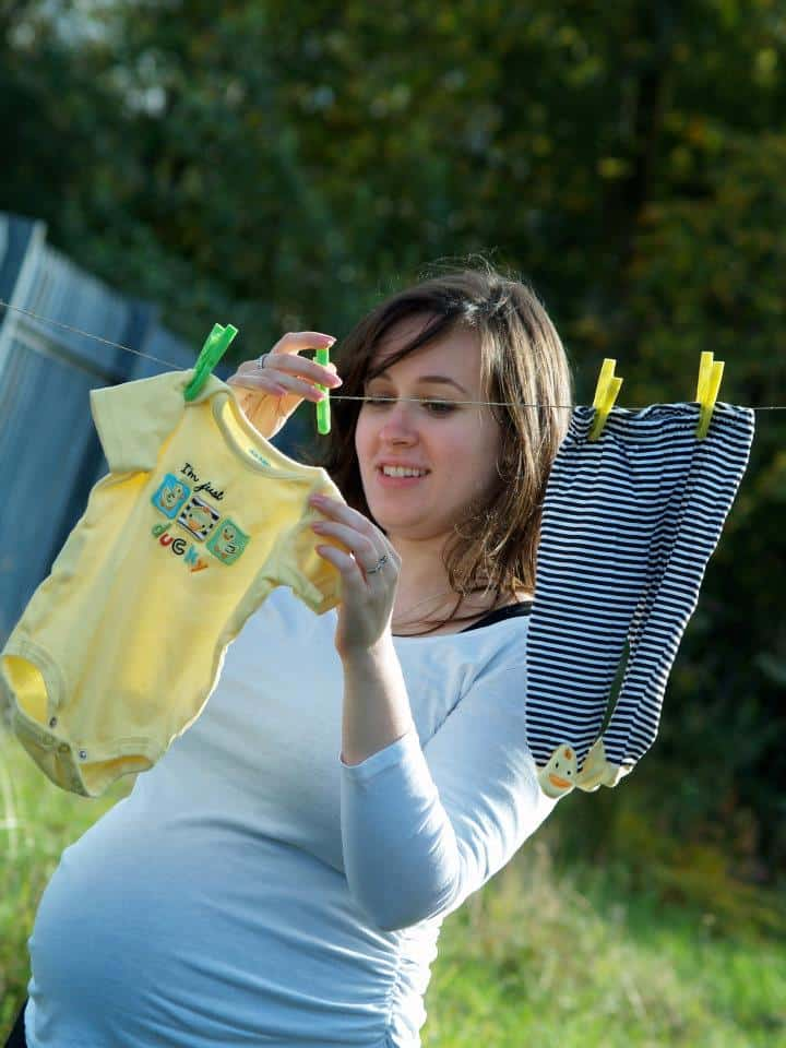Woman hanging baby clothes on a clothes line