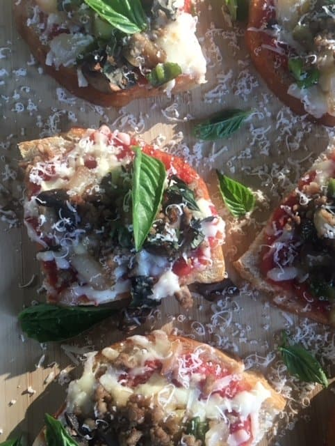 Sourdough homemade mini pizzas on a wooden board with fresh basil.