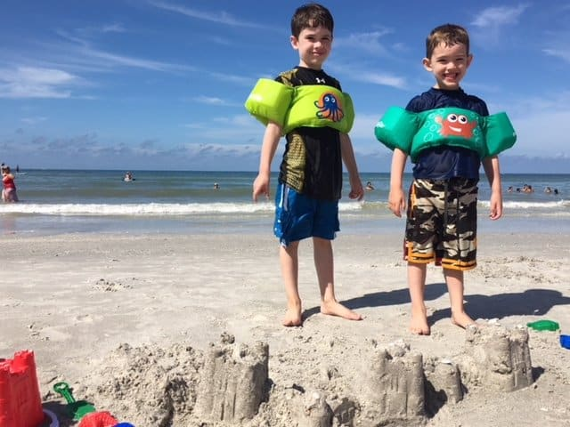 Two brothers building sandcastles at the beach