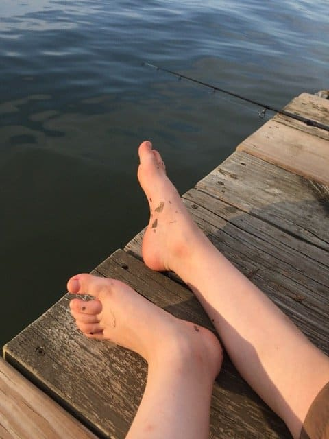 Childs feet on the edge of the dock at the lake.