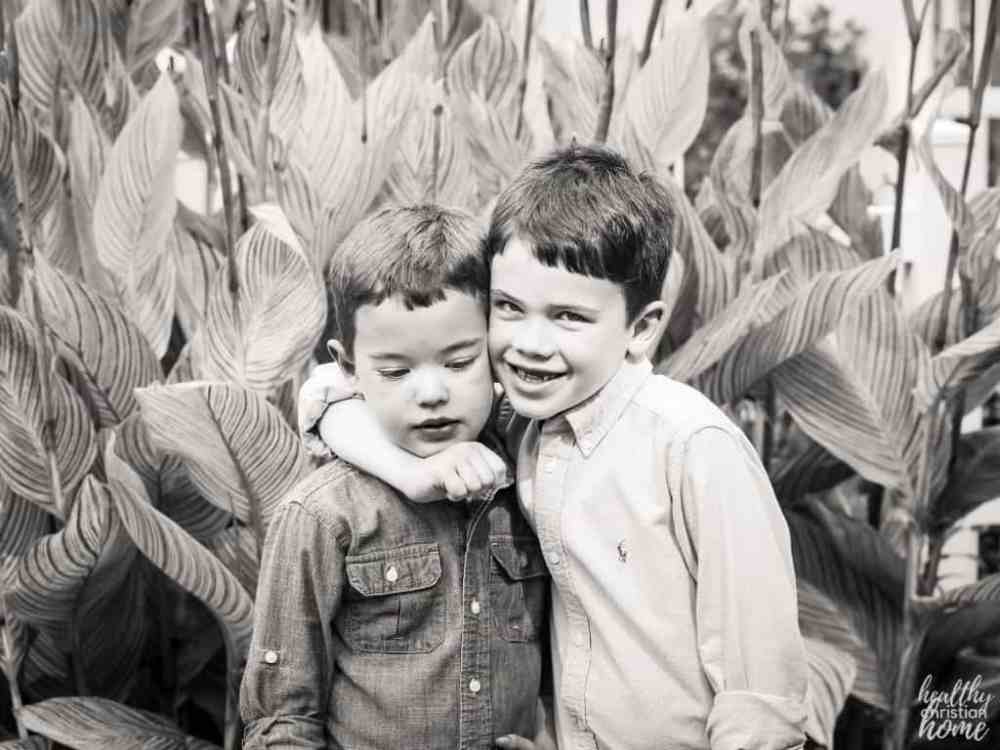 Black and white photo of an older brother hugging his younger brother.