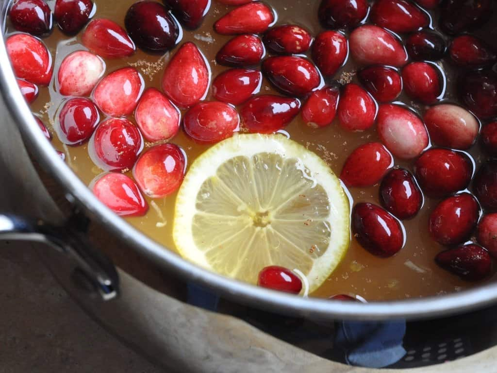 Cranberry wassail ingredients in a pot on the stove.
