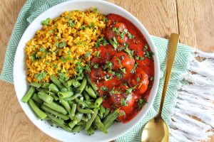 Balletjes in pikante tomatensaus met gekruide rijst en boontjes.