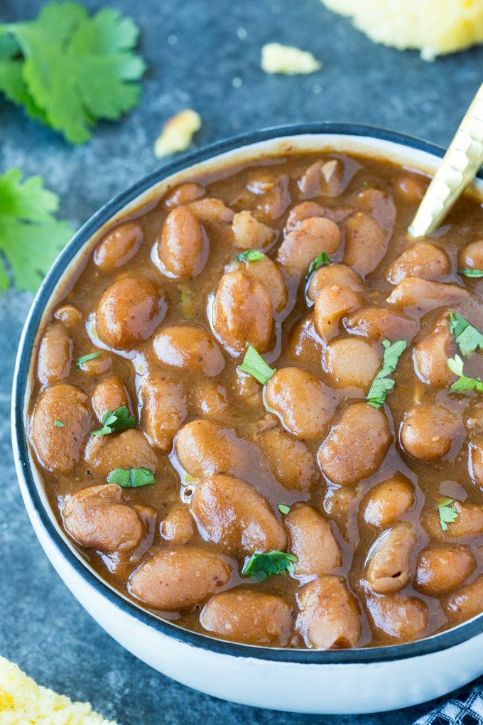 Instant Pot Ranch Style Beans in a white bowl with gold spoon