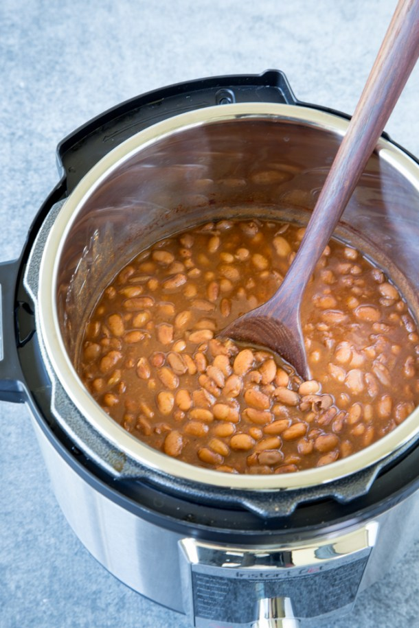 Cooked Instant Pot Ranch Style Beans in the Instant Pot with a wooded spoon