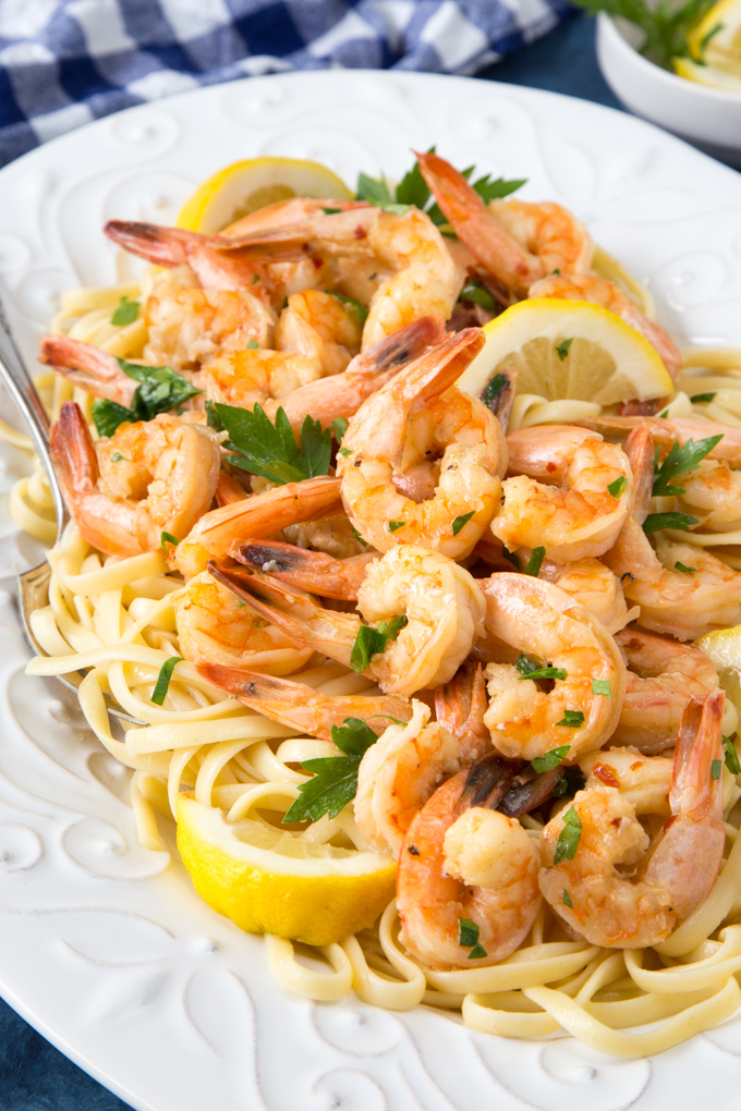 Cooked shrimp scampi over linguine noodles garnished with fresh parsley on a white plate