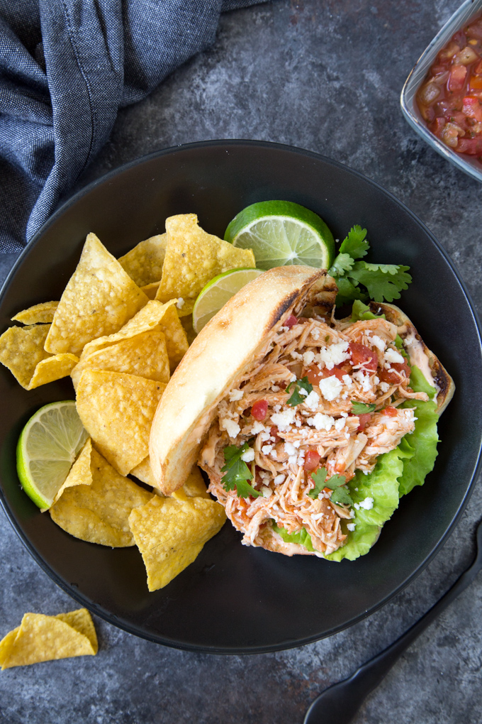 Mexican Salsa Shredded Chicken Sandwich- the shredded salsa chicken has been loaded into a bun and garnished with fresh cilantro. Served in a black bowl with tortilla chips