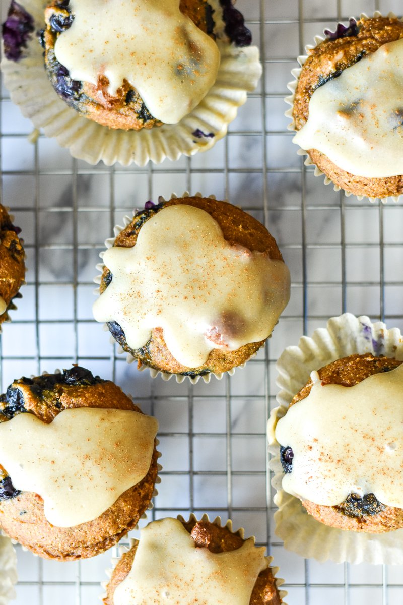 pumpkin blueberry muffins with tahini glaze on a cooling rack