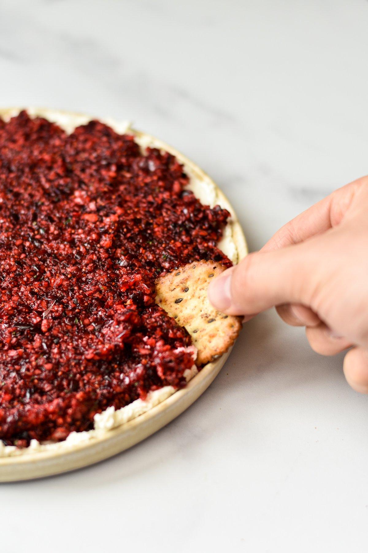 dipping a cracker into jalapeno cranberry dip