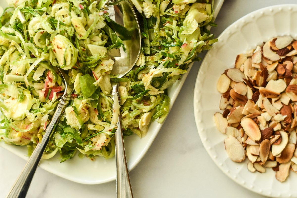 shaved brussels sprouts salad on a serving platter with toasted almonds on the side