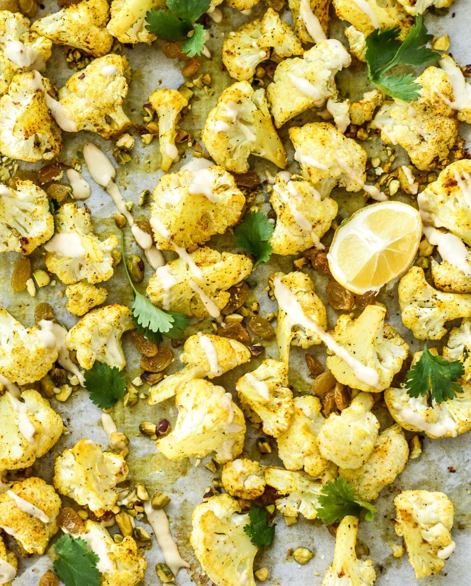 roasted cauliflower on a sheet pan with tahini and cilantro