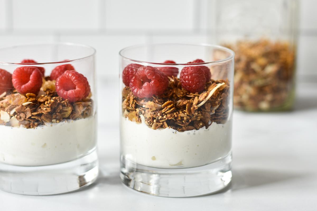 two glasses with yogurt, granola and fresh raspberries