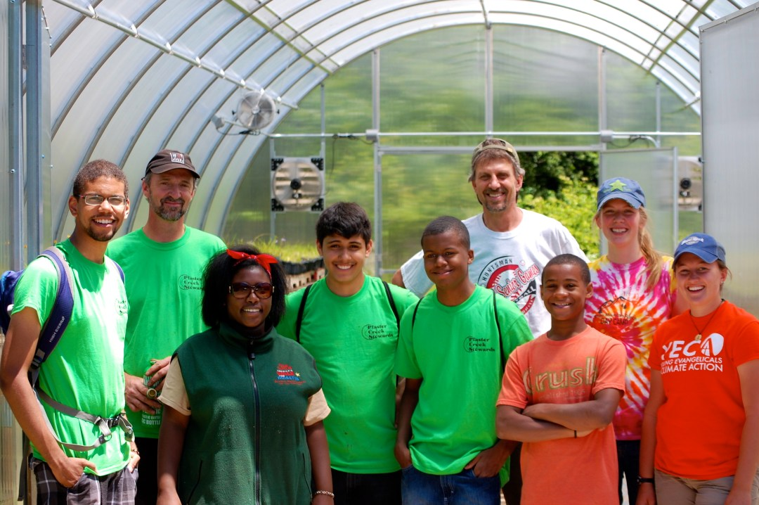 A group of 10 people stand together in front of a greenhouse