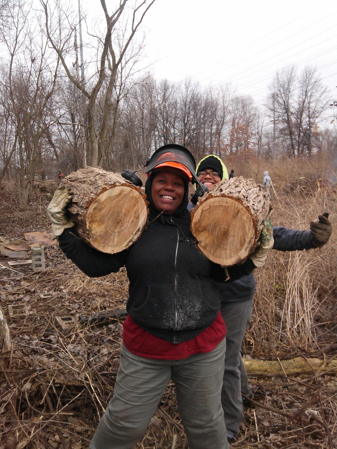 A crew leader of the Calumet Conservation Corps carries two big logs during a habitat restoration project.