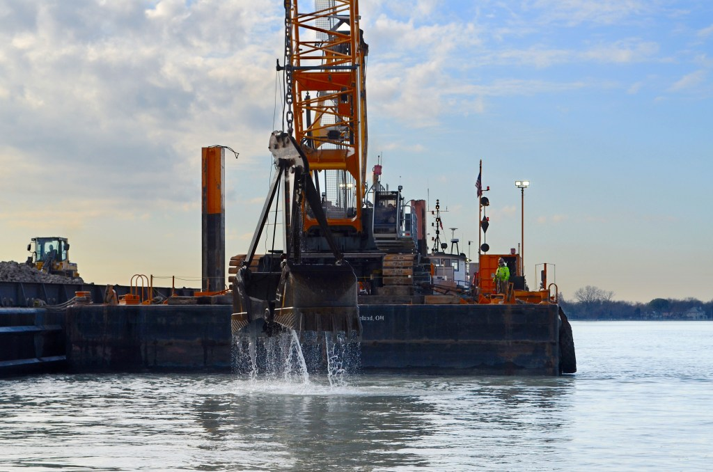An excavator on a barge drops material into water to build an artificial reef