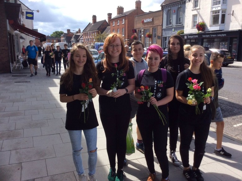 Give to improve your mental wellbeing: a group of young women giving flowers