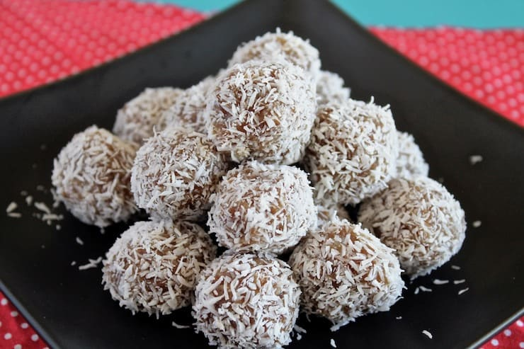 Close up of a pile of coconut date balls on a black plate on top of a red mat with white polka dots on a blue table