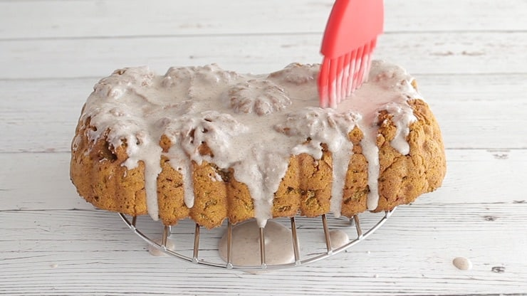 Red brush spreading white icing over paleo pumpkin bread sitting on metal wire over a white wooden surface