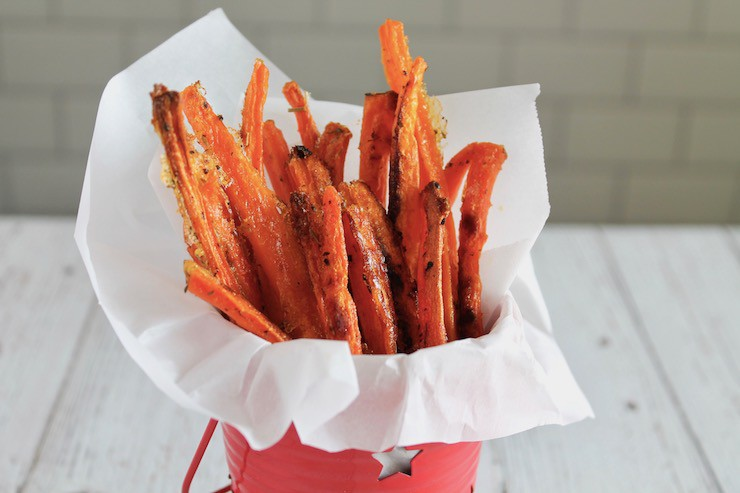 Carrot fries in a small red bucket lined with parchment paper on a white table