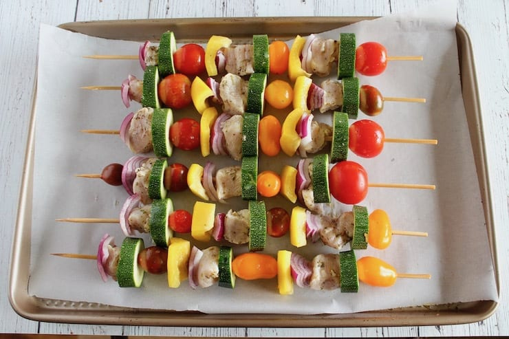 Overhead view of uncooked chicken kabob skewers with vegetables and chicken on wooden skewers