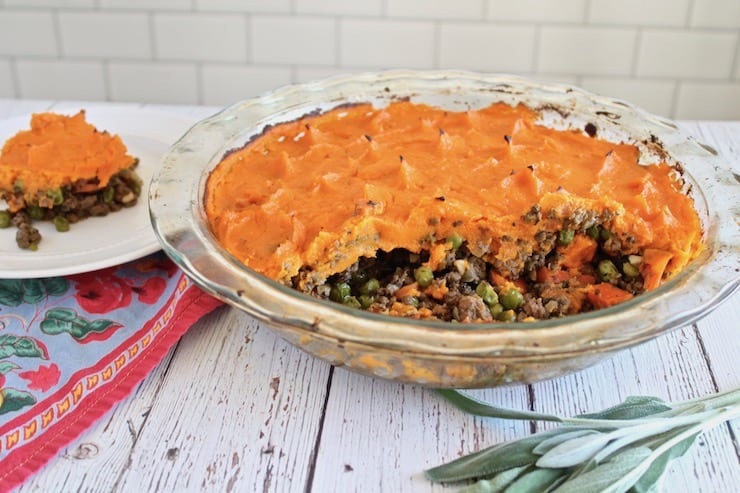 shepherd's pie with pieces taken out of it and a slice on a separate white plate behind it