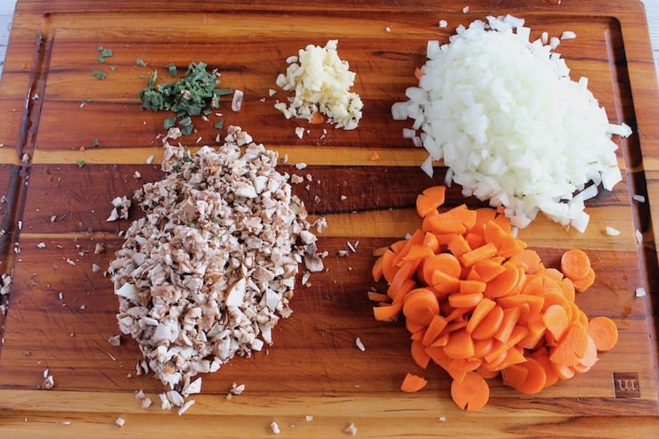 Chopped vegetables and herbs on a wooden cutting board