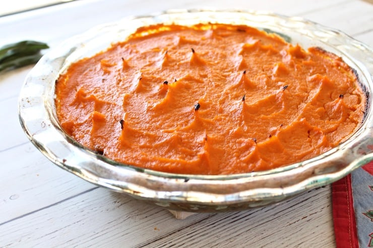 Whole shepherd's pie with sweet potato topping in a clear pie dish on a white wooden table