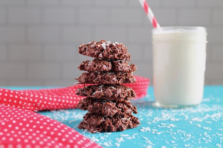 stacked coconut haystack cookies on a blue surface next to a glass of milk and a red and white polka dot napkin