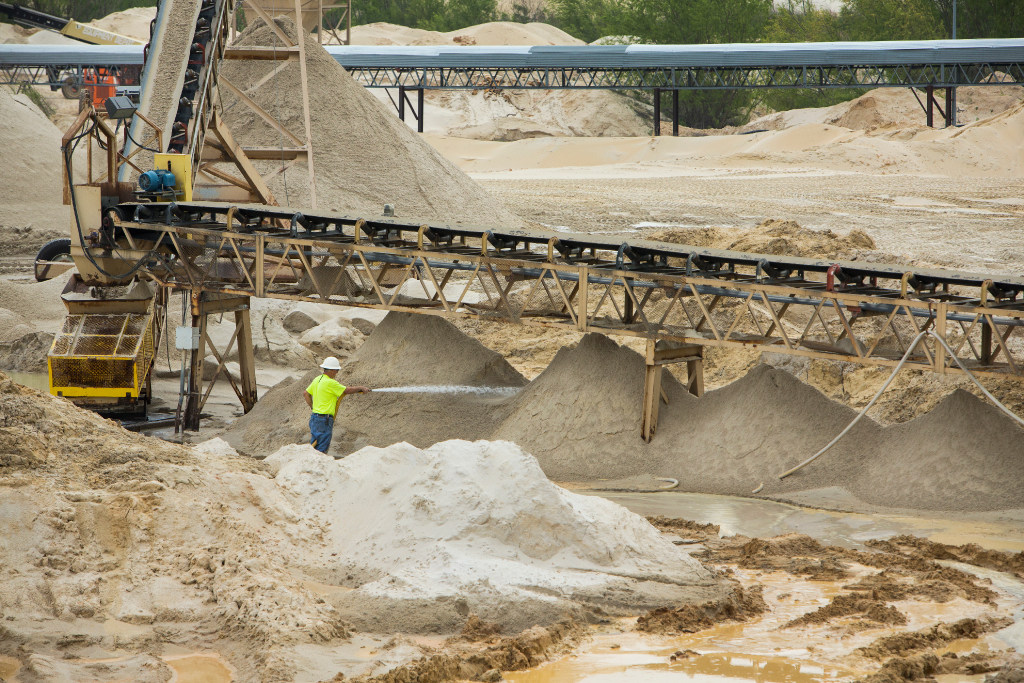 138e21a0c9f A worker sprays down piles of sand at the Superior Silica Sands sand mine  on Tuesday