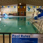 """This image shows an indoor swimming pool with the YMCA logo against the back wall, a blue water slide to the right, and a sign with """"Pool Rules"""" posted in the front."""