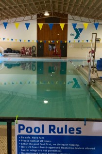 "This image shows an indoor swimming pool with the YMCA logo against the back wall, a blue water slide to the right, and a sign with ""Pool Rules"" posted in the front."
