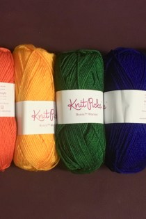 Skeins of yarn laid in a row: red, orange, yellow, green, blue, plum, purple.