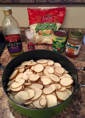 In the forefront: frying pan full of sliced potatoes. In the background: containers of olive oil, sea salt, shredded cabbage, refried beans, and salsa.