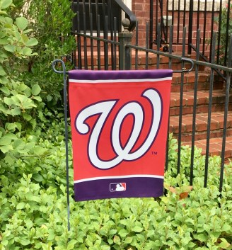 "Image of the ""Washington W,"" logo of the Washington Nationals baseball team, against green leaves and red brick stairs (in a neighbor's front yard)."