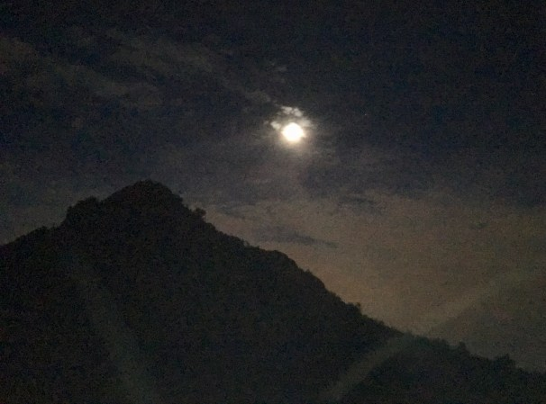 This photo taken once the sun set shows the black night sky with the shape of a mountain (darker than the sky) and the glowing moon (sphere of light).