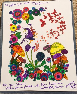 "This page from a coloring book shows butterflies swirling around a fairy, mushrooms, and flowers. The butterflies are a shade of red-orange, and the page is colorful. Around the edges are the words: ""For Sophia—with much love. May you bloom where you're planted, and flow freely on butterfly wings. Xoxoxo Beth."""