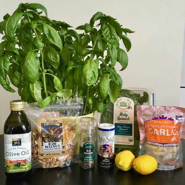 From left to right appears a bottle of Extra Virgin Olive Oil, a large basil plant, a bag of raw walnut pieces, black pepper and sea salt shakers, two full lemons, a package of pre-washed baby spinach, and a bag of peeled garlic.