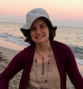 This head-shot shows Beth (a white woman with brown hair, wearing a floppy hiking hat) smiling, seated by the ocean as the sun sets.
