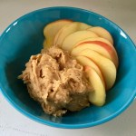 This photo shows a blue bowl against a white tabletop. Inside the bowl is the sweet spread (a light brown color with creamy texture) next to sliced apples (light, yellowish centers with red skin).