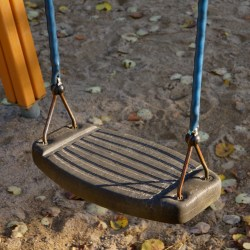 This image shows a brown swing seat held by two blue rubber cords. Sandy dirt with fallen leaves are in the background.