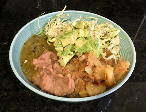 This bowl includes fried potatoes, shredded cabbage, refried beans, avocado, and tomatillo salsa.