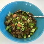This photo shows the final meal: a mixture of lentils and veggies topped with green onions—in a blue bowl against a white tabletop.