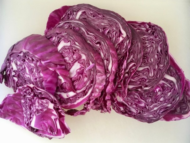 This image shows slices of red cabbage (purple and white in appearance) slightly overlapping with each other atop a white cutting board.