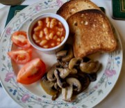 Gluten-free bread with baked beans, roasted mushrooms, and fresh tomato slices.